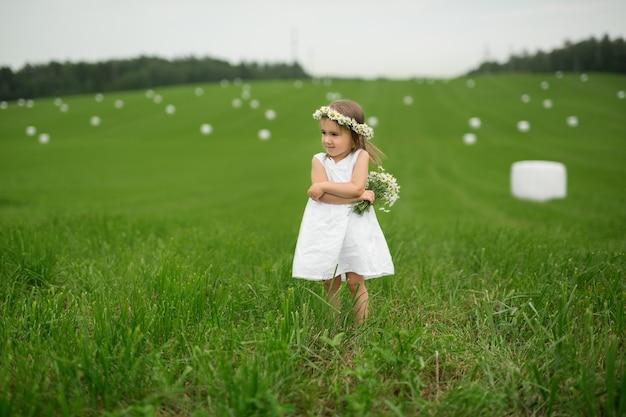Девушка в белом платье с венком на голове стоит в зеленом поле.