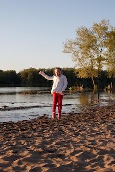 Девушка в белой куртке и розовых штанах прыгает по песку на пляже на берегу реки во время заката.