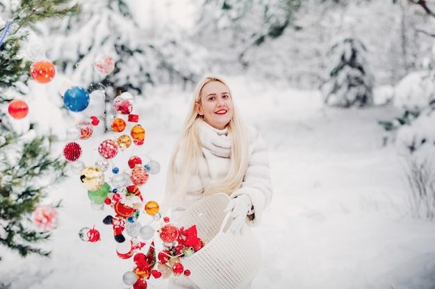 Девушка в белой куртке кидает елочные шары, чтобы украсить елку. девушка бросает елочные игрушки из корзины в зимний лес.