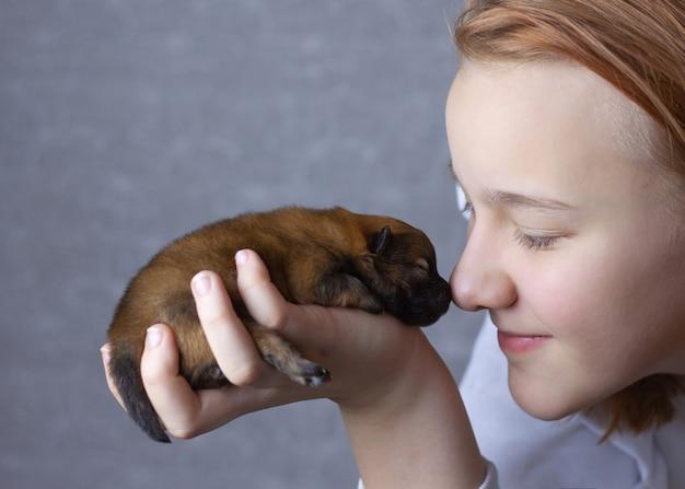 흰색 점퍼를 입은 소녀가 신생아 포메라니안 강아지를 얼굴 근처에 안고 코를 코에 대고 있습니다.