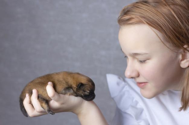 흰색 점퍼를 입은 소녀가 얼굴 근처에 신생아 포메라니안 강아지를 안고 있습니다.