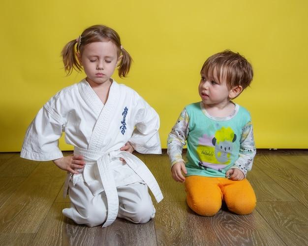 흰 기모노를 입은 소녀가 눈을 감고 명상하고 동생이 그녀를 따라 놀고 반복합니다.