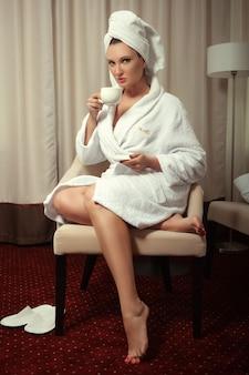 シャワーの後の白いローブの女の子は寝室で彼女のカップからコーヒーを飲みます