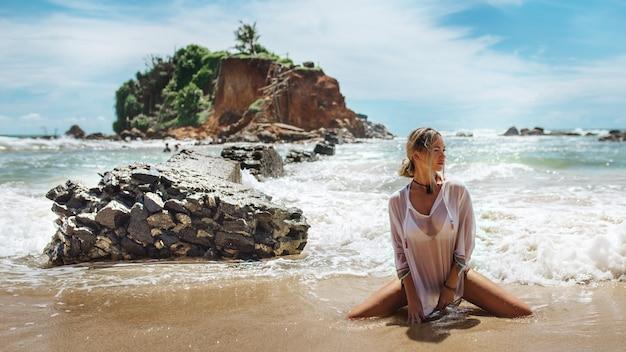 흰 셔츠를 입은 소녀가 바다 근처에서 무릎을 꿇고 있습니다.