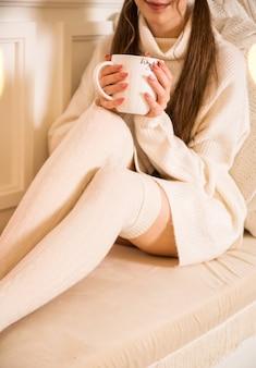 Девушка в белом свитере и леггинсах держит в руках большую белую чашку