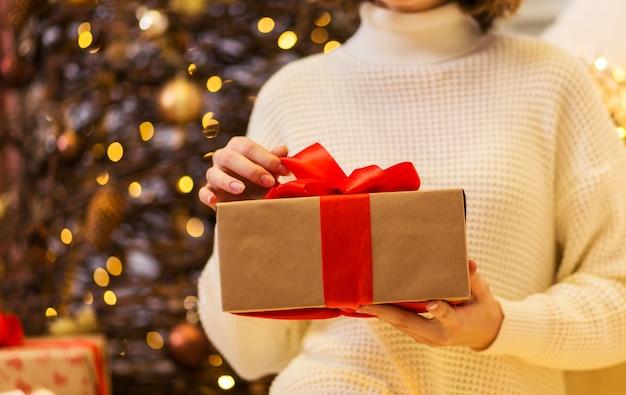 白いセーターを着た女の子が赤いリボンを手にプレゼントを持っています。クリスマスツリーの前に座っている女の子