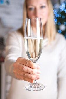 하얀 스웨터를 입은 소녀가 뻗은 손에 스파클링 와인 한 잔을 들고