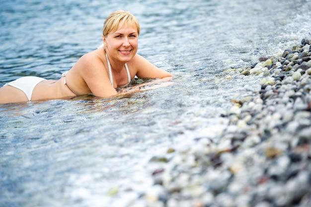 하얀 수영복을 입은 소녀가 바다에 누워 미소를 짓고 있습니다. 소녀는 물에 누워 웃습니다.터키,