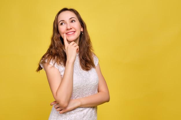 흰색 티셔츠와 노란색 배경에 갈색 청바지의 소녀는 꿈결 같은 표정으로 즐겁게 무언가를 생각합니다.