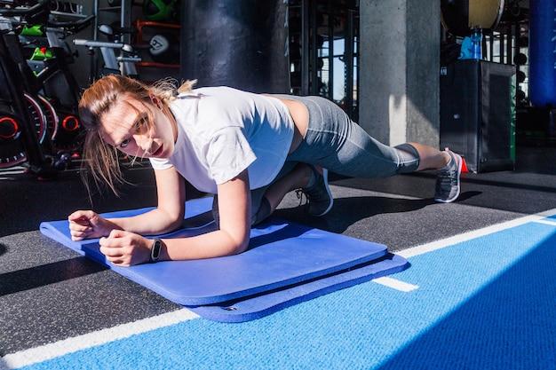 Девушка в белой футболке и серых леггинсах сидит на штанге на гимнастическом коврике в фитнес-клубе. солнечный свет и жесткие тени в фитнес-клубе. горизонтальное фото