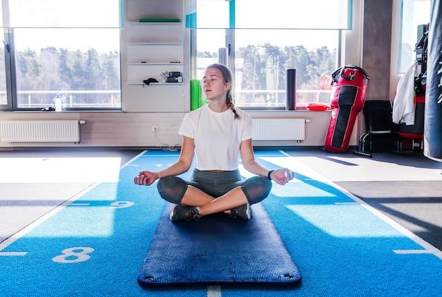 Девушка в белой футболке и серых леггинсах сидит на гимнастическом коврике в позе лотоса в фитнес-клубе с закрытыми глазами и медитирует. горизонтальное фото