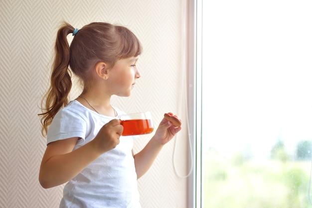 白いtシャツを着た女の子が、窓際に立って見ている赤いハートの形をしたお茶と肝臓を持っています。美味しいおやつ。自宅で安全、パンデミック時の自己隔離。