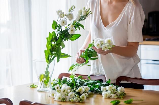 白いtシャツを着た女の子が白いバラの花束を準備してから、キッチンのテーブルの上に花瓶に入れています。ライフスタイルのコンセプト