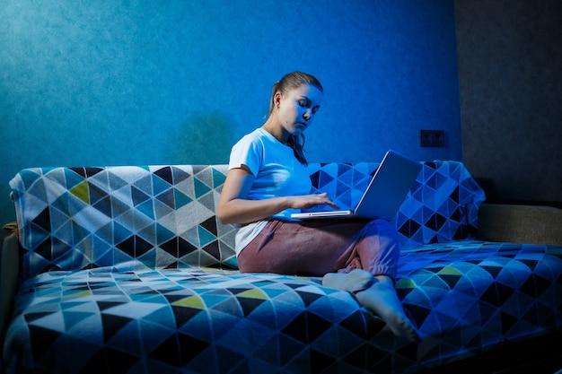 Девушка в белой футболке сидит дома на диване с ноутбуком на коленях и смотрит в экран. читает новую важную информацию. поиск новостей Premium Фотографии