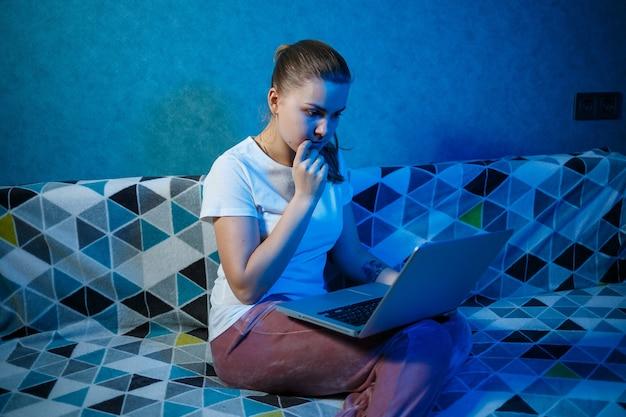 白いtシャツを着た女の子が自宅のソファに座って、ラップトップを膝の上に置き、画面を見ています。新しい重要な情報を読み取ります。ニュースを検索