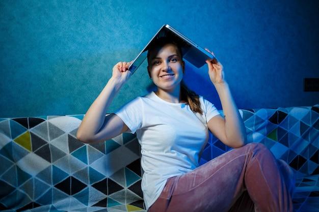 Девушка в белой футболке сидит дома на диване со своим любимым ноутбуком. надеть компьютер на голову