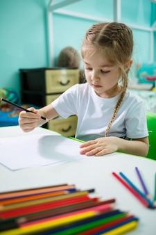 白いtシャツを着た女の子がテーブルの自分の部屋に座って、色鉛筆で描きます