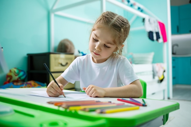 Девушка в белой футболке сидит в своей комнате за столом и рисует цветными карандашами