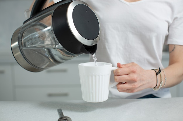 白いtシャツを着た女の子がやかんから白いマグカップにきれいな水を注ぐ健康的なライフスタイル高品質の写真