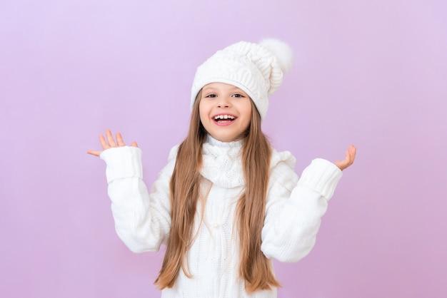 하얀 겨울 모자를 쓴 소녀가 팔을 흔들며 기뻐하고 있습니다.