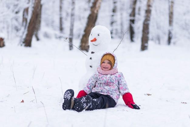 冬の森の少女が雪だるまの隣に立っている