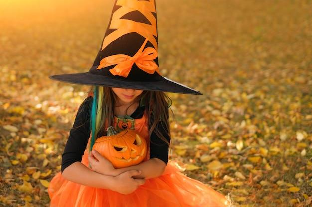 魔女の衣装と大きな帽子をかぶった女の子がカボチャを抱きしめます