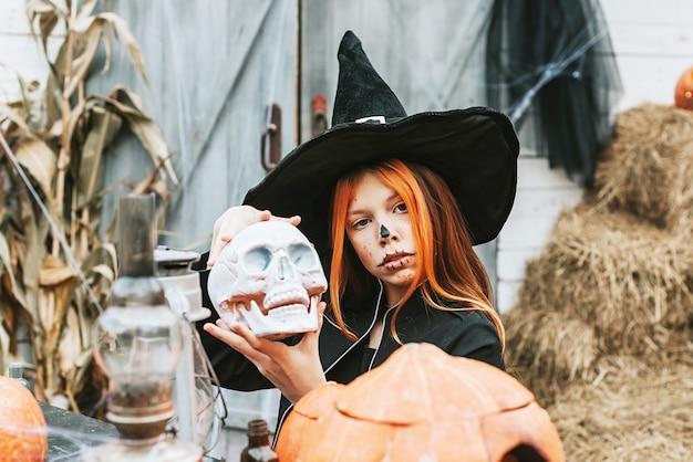 Девушка в костюме ведьмы веселится на вечеринке в честь хэллоуина на украшенном крыльце