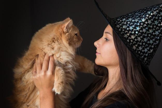 魔女の衣装を着た女の子は、暗い背景にハロウィーンの赤い猫を保持しています