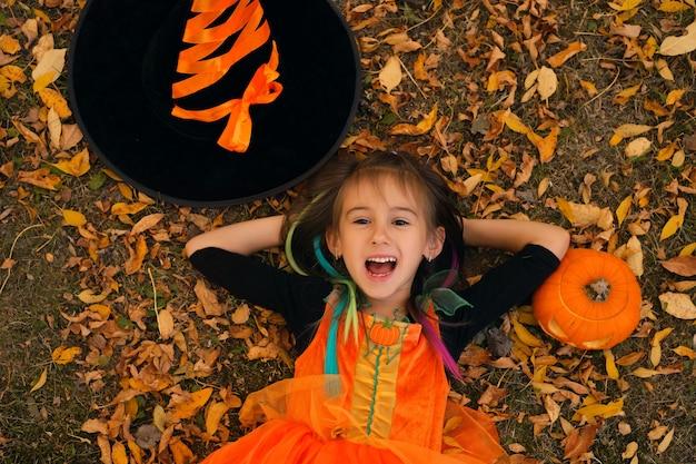 魔女の衣装を着た女の子がカボチャと帽子の横にある紅葉に横たわっています