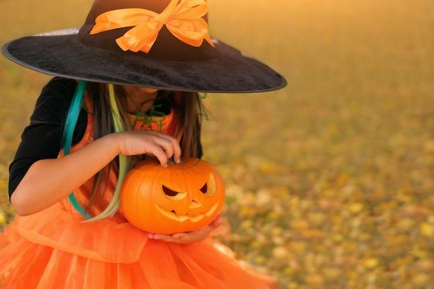 魔女のドレスと帽子をかぶった女の子がジャック・オー・ランタンの顔を彫ったカボチャを持っています