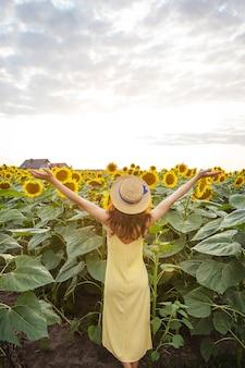 노란 드레스와 밀짚 모자를 쓴 소녀가 손을 들고 등을 대고 서서 넓은 해바라기 밭에 해바라기 꽃다발을 들고 있습니다. 아름다운 화창한 날.