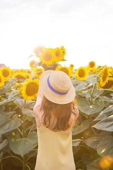 노란 드레스를 입고 밀짚모자를 쓴 소녀가 등을 대고 커다란 해바라기 밭에 해바라기 꽃다발을 들고 있습니다. 아름다운 화창한 날.