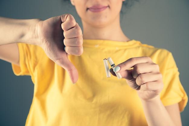 壊れたタバコを持っている黄色のドレスを着た女の子