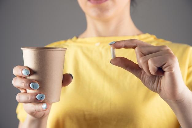 Девушка в желтом платье держит таблетку и стакан воды