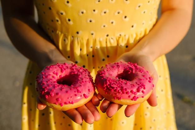 노란 드레스를 입은 소녀가 식욕을 돋우는 분홍색 도넛을 손에 들고 있다