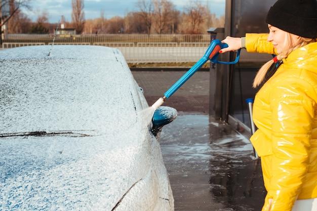 イエロージャケットの女の子がセルフサービスの洗車で車を洗う