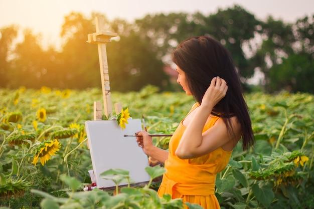 黄色の長いドレスを着た女の子が日没時にひまわり畑のイーゼルに帆布を描く
