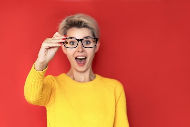 黄色いセーターを着た女の子が眼鏡を通して見る