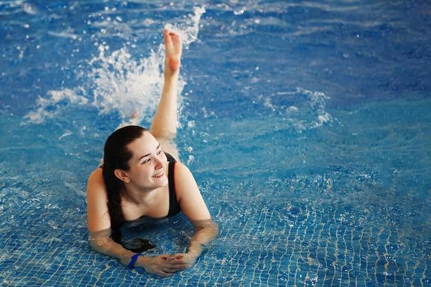 푸른 물이 있는 수영장의 아쿠아파크에 있는 소녀가 웃고 미소 짓습니다