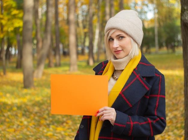 가을 공원에 있는 한 소녀가 당신의 글을 위한 종이 한 장을 들고 있습니다. 광고 책자