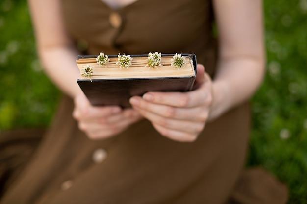 オリーブのドレスを着た女の子が手に花の本を持っています