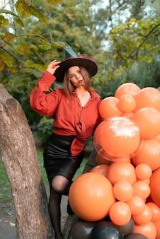 オレンジ色のシャツ、黒いスカート、風船の背景に魔女の帽子をかぶった女の子。ハロウィーン