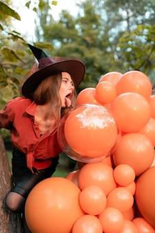 オレンジ色のシャツを着た女の子と風船の背景に魔女の帽子。ハロウィーン。舌を見せます