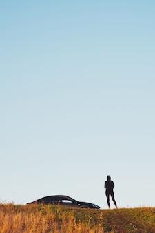 검은 옷을 입은 소녀가 언덕에 검은 세단 자동차 옆에 서서, 흐린 하늘, 복사 공간
