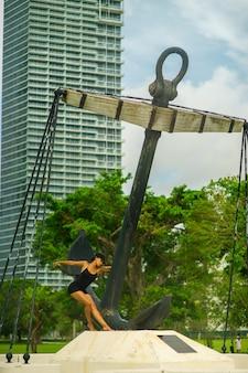 黒のショートパンツとトップスの女の子が巨大な錨の近くでポーズをとる。マイアミ。