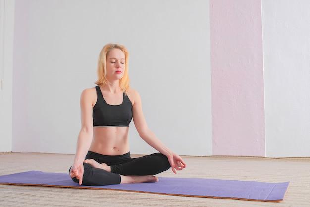 Девушка в черной спортивной одежде сидит в позе лотоса и выполняет мудры