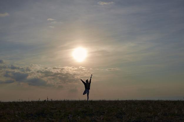 黒いスポーツウェアを着た女の子が山の頂上に立って、手を背景に...