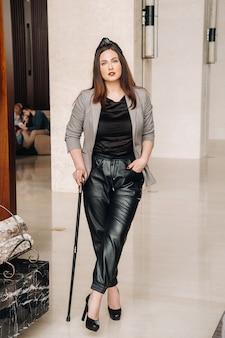 Девушка в черных брюках и куртке с тростью в интерьере.