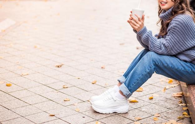 Девушка в синих джинсах и свитере сидит на улице и позирует со стаканом горячего шоколада в руках. фото