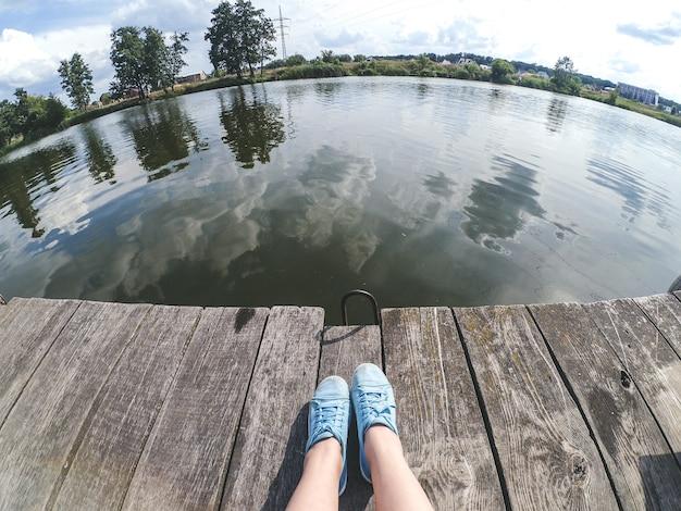 파란 신발을 신고 호수 강 근처의 나무 부두에 앉아 있는 소녀